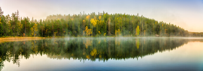 Autumn forest with morning mist reflected in the lake at dawn