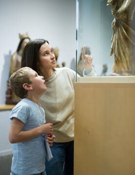 Young female tutor with boy looking at exposition in museum of ancient sculpture, pointing to something