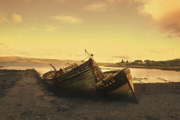 Abandoned wrecked boat stuck in sand. Old wooden boat on the sandy shore of beach. Sunset on the beach