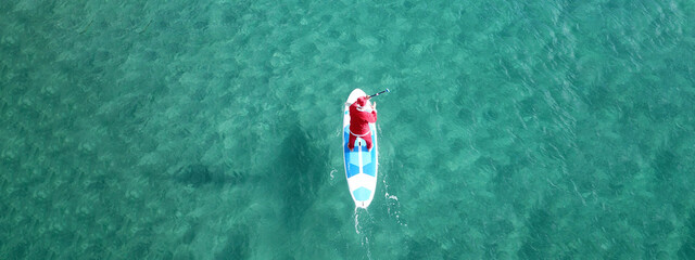 Aerial drone ultra wide photo of Santa Claus paddle surfing in Caribbean turquoise exotic crystal clear clear sea
