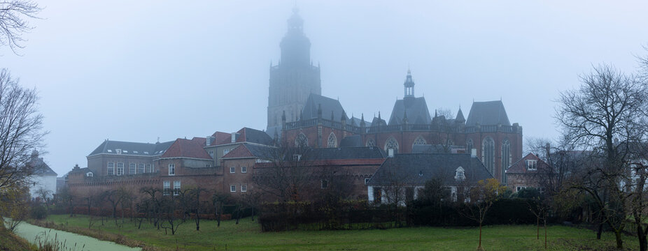 Panorama of historic city centre with church tower and medieval buildings in Zutphen, The Netherlands, seen from the city gardens with strong mist making it a mysterious view of the heritage sites.