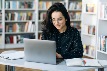 Obraz Busy caucasian young woman, in eyeglasses is sitting at the desk while remote work from home and chatting online using a laptop - fototapety do salonu