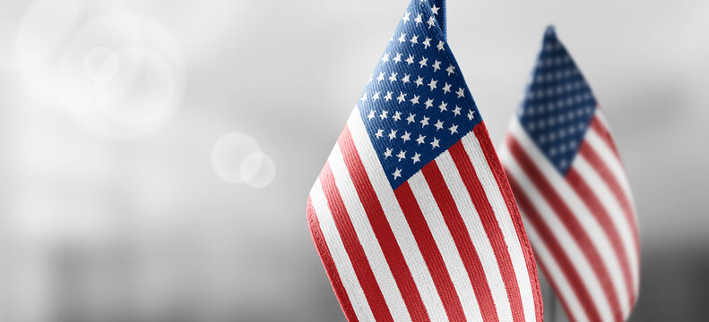 Small national flags of the United States on a light blurry background