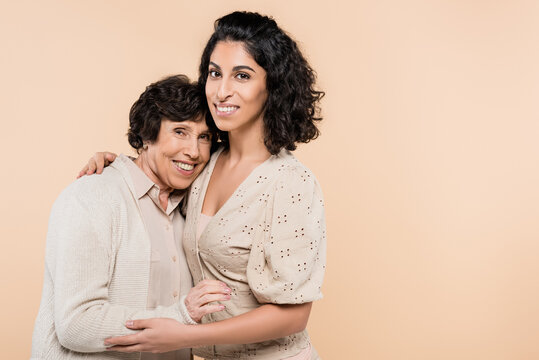 Cheerful hispanic woman hugging senior mother isolated on beige, two generations of women