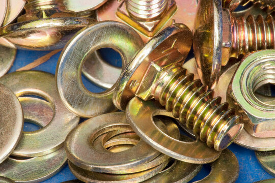 Close-up of yellow metal screws and washers.