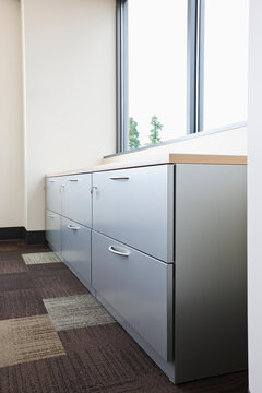 Filing cabinet and window in office.