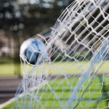 Soccer ball hitting the back of a football net.