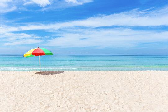 A colourful umbrella on white beach with beautiful sky.