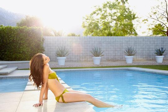 Young woman in a bikini on the edge of a swimming pool