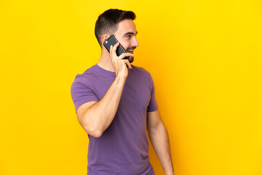 Young caucasian handsome man isolated on yellow background keeping a conversation with the mobile phone with someone