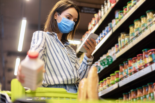 Woman in mask using smartphone standing in store