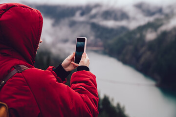 Anonymous traveler using smartphone to take picture of natural landscape
