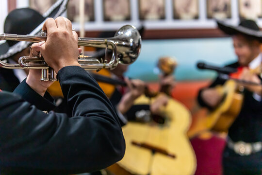 Selective focus of young man mariachi dressed in black suit, blowing trumpet with orchestra playing at the altar during remembrance festival dia de los muertos
