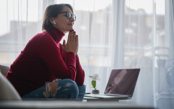 Beautiful adult woman in glasses sitting on the sofa at home meditating and relaxing in front of laptop screen