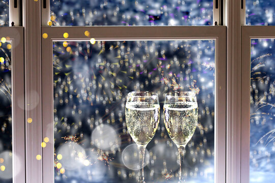 New Years background with two glasses of champagne, falling snow and firework display viewed by window.
