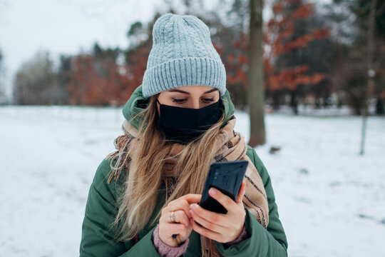 Woman wears mask outdoors during coronavirus covid-19 pandemic. Girl using smartphone in snowy winter park