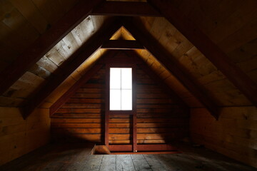 Obraz Wooden attic under a sloped roof with bright window and entrance visible in the floor - fototapety do salonu