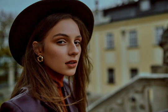 Close up fashion portrait of elegant woman wearing trendy earrings, fedora hat, posing at street. Copy, empty space for text