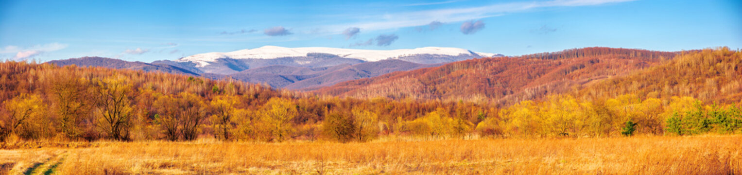 sunny evening in mountainous countryside. beautiful panorama of rural landscape in spring. snow capped ridge in the distance. wonderful weather with clouds on the blue sky