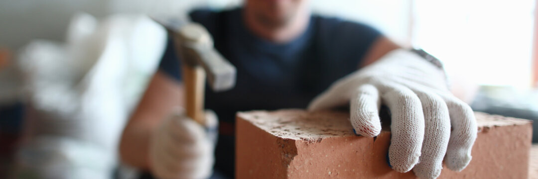 Close up of male builder hands using hammer while building masonry construction