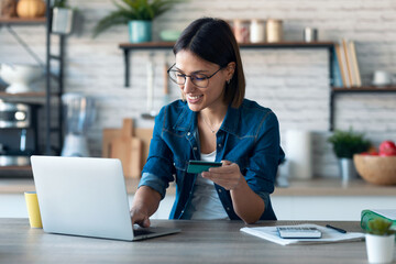 Cute young woman holding white credit card for shopping online with computer while sitting in the kitchen at home. - fototapety na wymiar