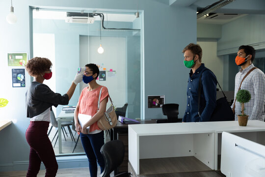 Mixed race woman wearing face mask checking temperature of colleagues