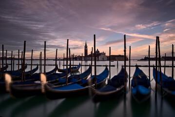 Venezia, gondole in piazza San Marco con sullo sfondo la chiesa di San Giorgio maggiore illuminata dal tramonto