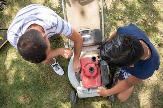 Overhead view of father and son fixing lawn mower in garden