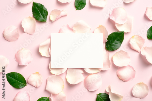 Blank paper card mockup with rose petals and green leaves on pink background. Flat lay, view from above. Greeting card template for Valentines Day, Mothers Day, birthday.