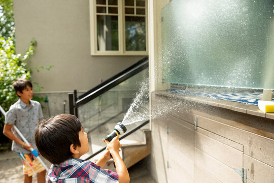 Boy cleaning glass wall on house exterior