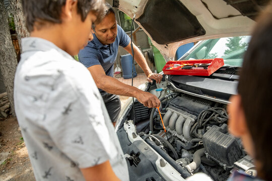 Man and sons inspecting car engine with hood up