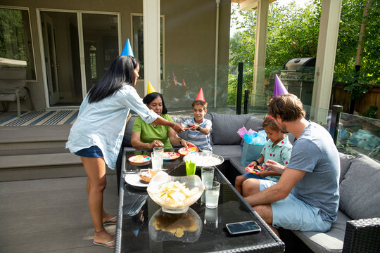 Family wearing cone hats celebrating birthday on terrace
