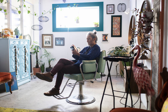 Hairdresser owner texting on phone in startup salon