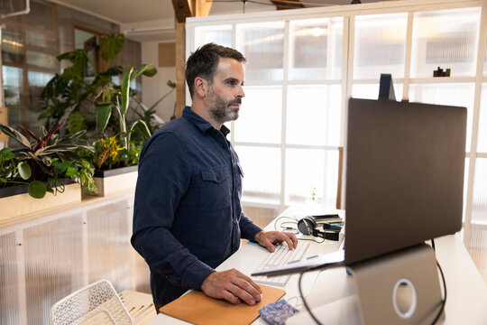 Man standing working at computer in office