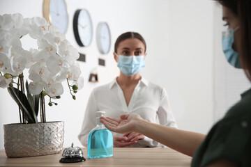 Woman applying antiseptic gel at hotel reception, closeup