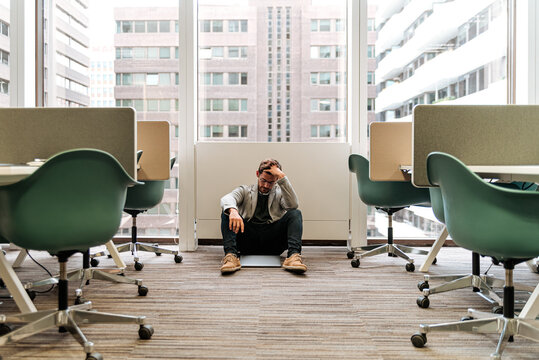Frustrated young man sitting on floor in office