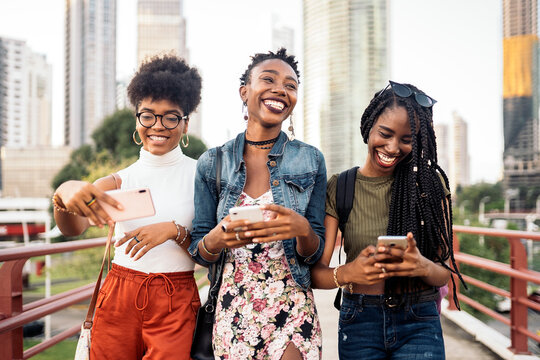 Three afro women using mobile phone