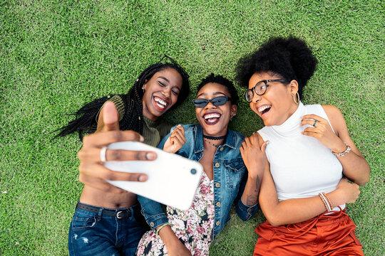 Three afro friends taking photo
