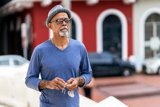 Senior black man standing in street.
