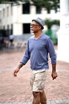 Senior black man walking down the street.