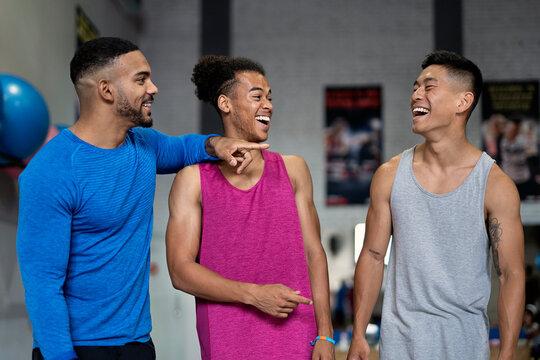 Three muscular man talking in a gym.