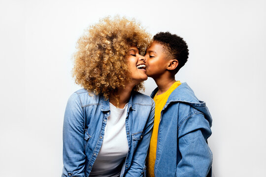 Black boy in studio kissing his mom.