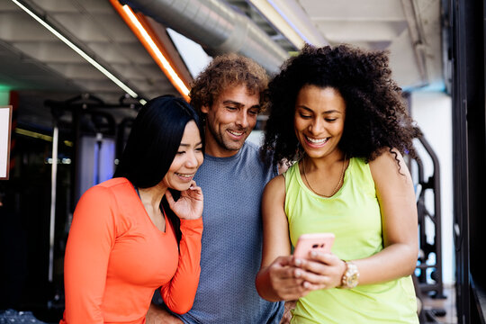Group of friends looking at smartphone at gym.