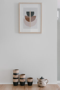Crockery on wooden floor at white wall with painting