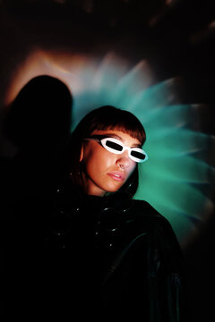 girl in fashion future glasses wearing black with blue light behind