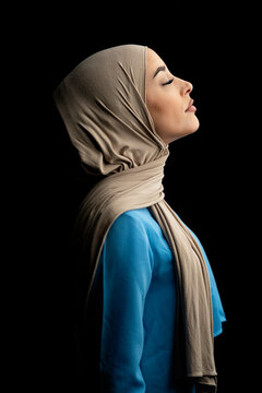 Side View of Muslim Woman Over Black Background