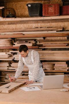 Joiner making marks on wooden plank