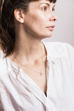 Close-up of woman wearing necklace looking away in studio