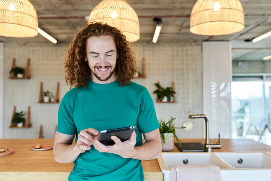 Handsome man using digital tablet while standing at studio apartment