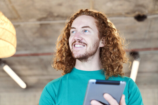 Male hipster with long hair looking away while using digital tablet at home